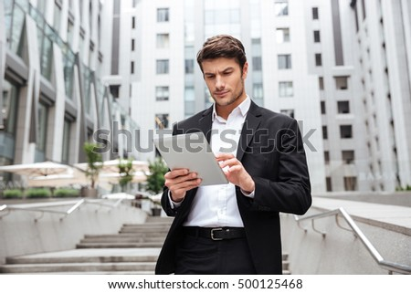 Serious concentretaed young businessman walking and using tablet in the city