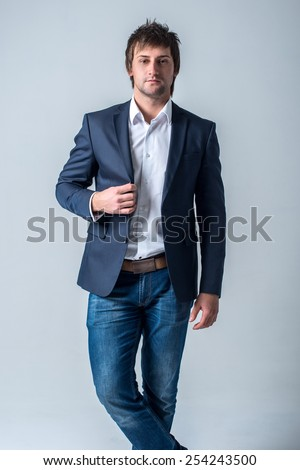 Serious confident cool attractive guy in jeans and jacket stand against the wall. - stock photo