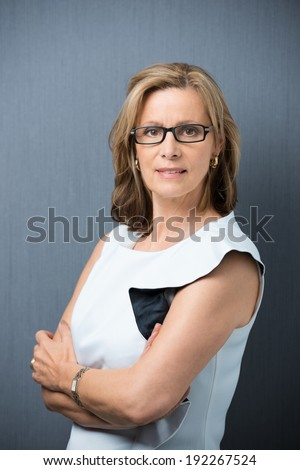Serious confident middle-aged woman wearing spectacles standing with her arms crossed looking intently at the camera - stock photo
