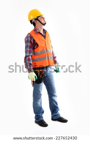 Serious construction worker in yellow helmet and orange waistcoat looking up. Full length studio shot isolated on white.  - stock photo