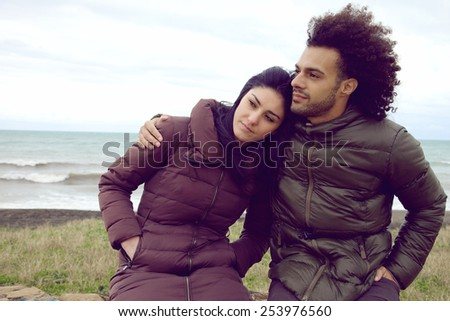 Serious cool fashion couple in front of the ocean