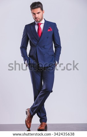 serious corporate man looking at the camera while having both hands in pockets and legs crossed - stock photo