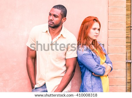 Serious couple back to back with love problems looking away - Mixed race friends in upset mood standing outside - Breakup of a relationship concept with feeling of sadness and anger - Focus on male - stock photo