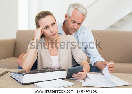 Serious couple calculating their bills at the couch at home in the living room - stock photo