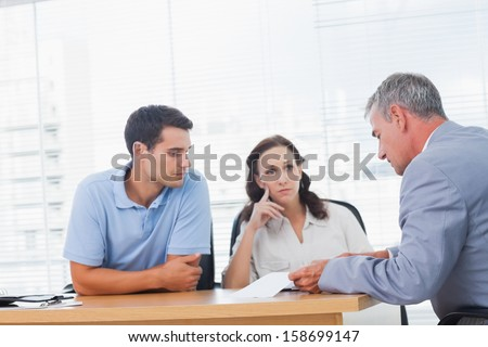 Serious couple negotiating with real estate agent in bright office