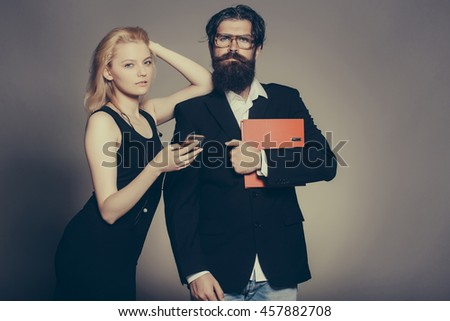 Serious couple of young blond woman in black dress with smartphone and handsome bearded hipster man in suit glasses with folder on grey wall