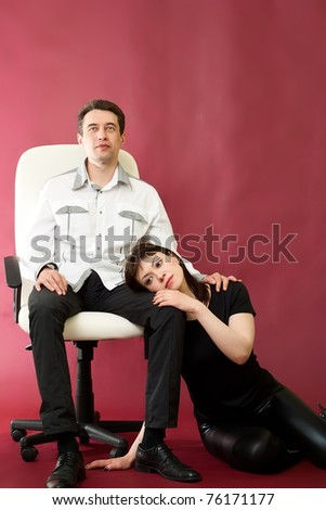 Serious couple on armchair on red burgundy background - stock photo