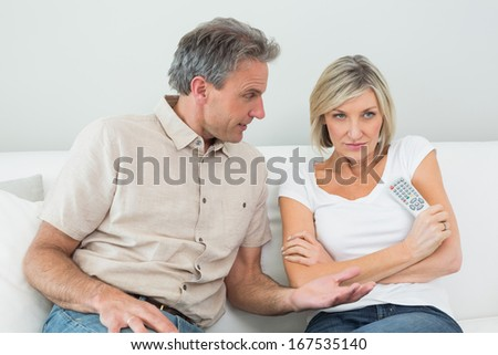 Serious couple watching tv in the living room at home - stock photo