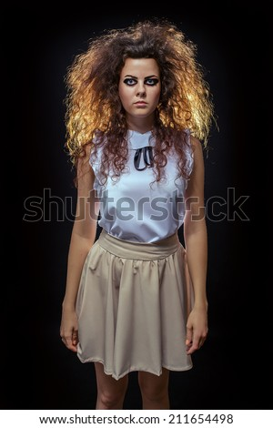 serious crazy woman with fluffy hair looking at camera