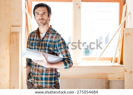 Serious creator. Confident young man holding blueprint and looking at camera while standing at his workshop - stock photo