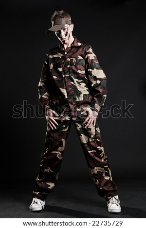 serious dancer in camouflage posing over dark background