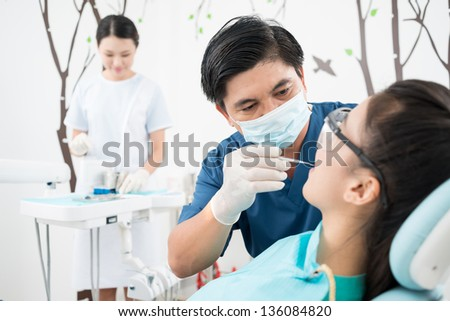 Serious dentist examining a patient, his assistant being in the background - stock photo