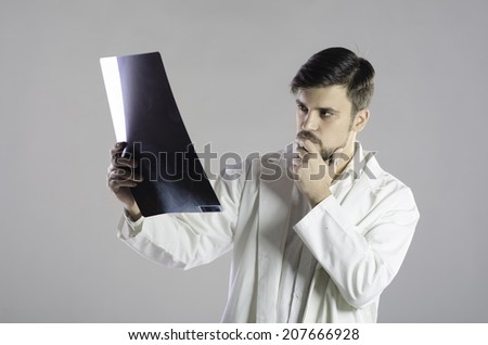Serious doctor examining x ray