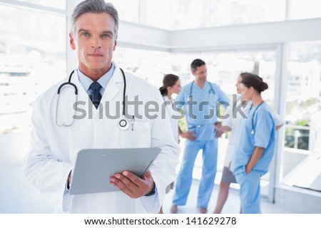 Serious doctor holding clipboard in front of his medical team - stock photo