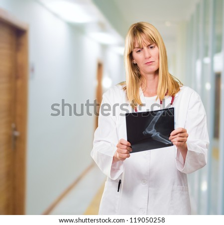 serious doctor looking at an x-ray in a passageway, indoor - stock photo