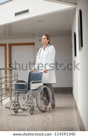 Serious doctor pushing a wheelchair in the corridor in hospital hallway - stock photo
