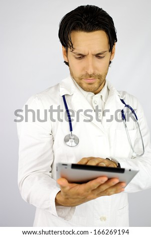 Serious doctor researching treatment with tablet - stock photo