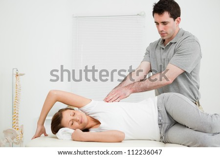 Serious doctor using his fingertips on a patient in a bright room