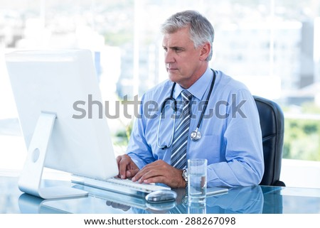 Serious doctor working on computer at his desk in medical office
