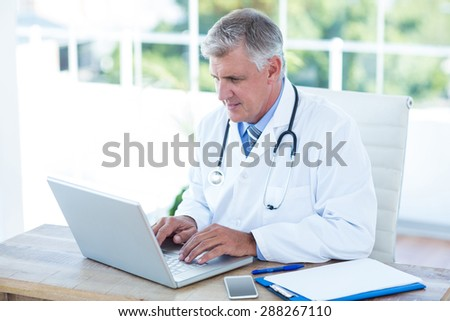 Serious doctor working on laptop at his desk in medical office - stock photo