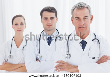 Serious doctors posing together in bright office