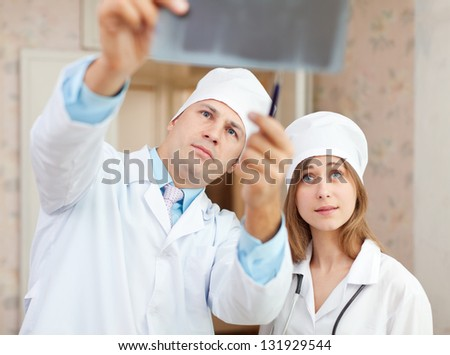 serious  doctors stares x-ray scan  in clinic. Focus on man - stock photo