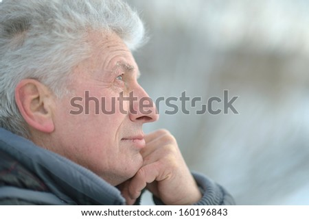 serious elderly man out for a walk in winter