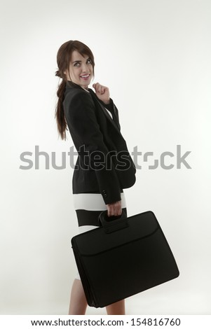 Serious elegant businesswoman holding briefcase - stock photo