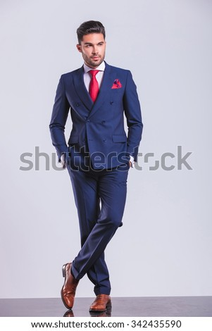serious elegant man posing with hands in pockets while looking away - stock photo