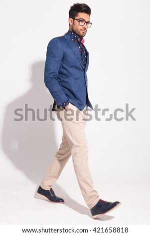 serious elegant man with hands in pockets walking in studio