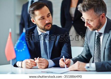 Serious employee looking at business partner signing contract with his colleagues on background - stock photo