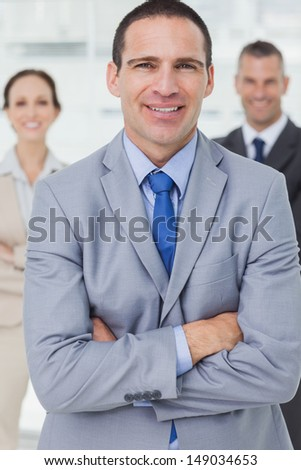 Serious entrepreneur in bright office posing with his colleagues on background