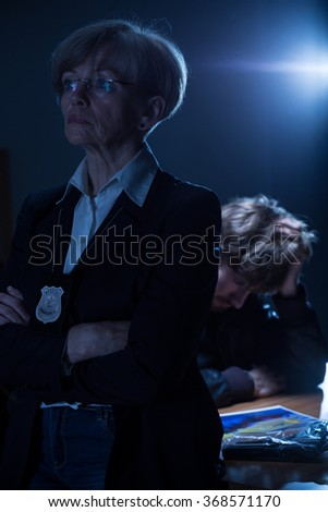 Serious experienced policewoman with badge and worried arrested man - stock photo