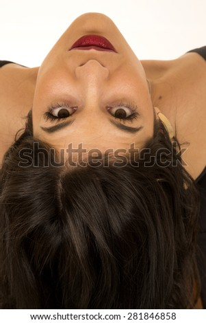 Serious expression on a gorgeous female unique portrait upside down staring into camera with a white background - stock photo