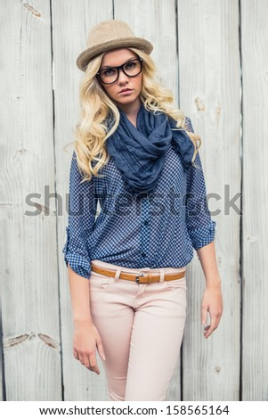Serious fashionable blonde posing outdoors on wooden background - stock photo