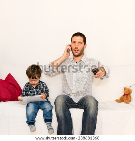 Serious father making a phone call and watching tv while son is playing with tablet on a white sofa with a red pillow and a bear toy - stock photo