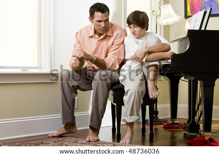 Serious father talking to teenage son at home by piano - stock photo