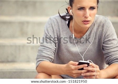 Serious female athlete listening to mp3 music during her break - stock photo