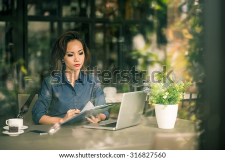 Serious female entrepreneur sitting in a cafe and reading business document - stock photo