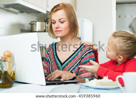 Serious female freelancer working with laptop in the kitchen, little girl distracting her - stock photo