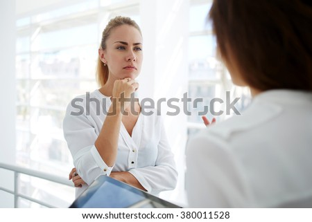 Serious female proud ceo attentively listening her partner which holding touch pad while standing in office hallway, young woman subordinate reporting to her managing director with digital tablet