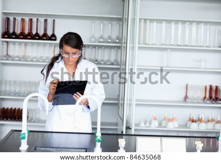Serious female scientist writing on a clipboard in a laboratory - stock photo