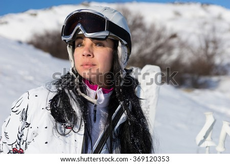 Serious female skier with headgear and goggles standing in front of snowy hill and ski equipment stuck in ground