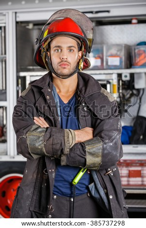 Serious Firefighter Standing Arms Crossed Against Firetruck
