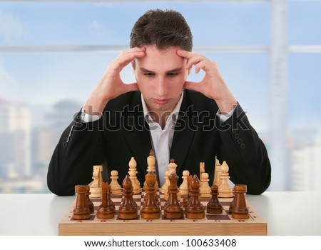 serious focused man thinks  on game of chess - stock photo