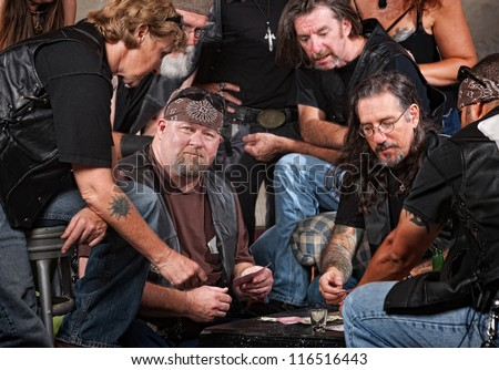 Serious gang members playing cards and drinking