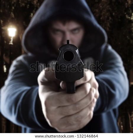 Serious gangster is aiming a gun to you