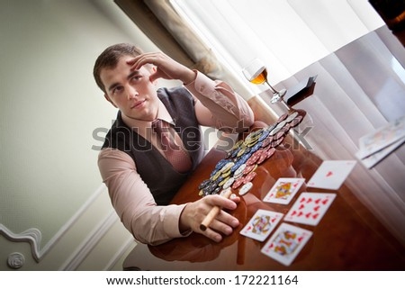 Serious gentleman open his cards in poker.  - stock photo