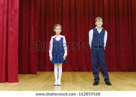 Serious girl and happy boy in school uniform stand on stage with red curtains. - stock photo