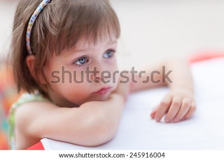 Serious Girl. Cute little girl looking for someone or something at coffee table. Closeup portrait with shallow depth of field - stock photo